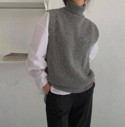 Woman in a grey turtleneck sweater with hands in pockets chilling